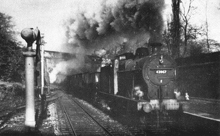 Steam age freight at Marple in 1964. An Up Goods Train of coal empties enters the north end of the station behind a Fowler 4F 0.6.0 43967